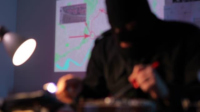 vídeos y material grabado en eventos de stock de terrorista enmascarado haciendo una bomba de tiempo en el taller - haz de luz