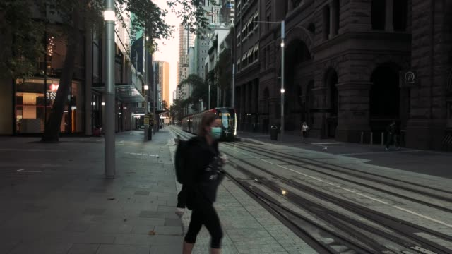 masked woman crosses the light rail line during morning peak hour in sydney, cbd on march 31, 2020 in sydney, australia. . public gatherings are now... - home economics点の映像素材/bロール