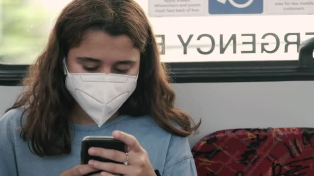 masked woman is seen texting while traveling on a bus on march 26, 2020 in sydney, australia. public gatherings are now limited to two people, as the... - using phone stock videos & royalty-free footage