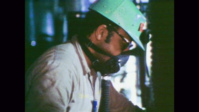 vidéos et rushes de 1978 masked workers create polyvinylchloride (pvc) resin - masque de protection
