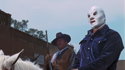 vídeos y material grabado en eventos de stock de masked wrestler on a horse talks to a man and they start arguing. the two men start a fight. featuring el santo, el enmascarado de plata. - western usa