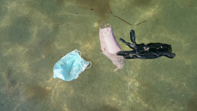 masks and disposable gloves polluting ocean - latex glove stock videos & royalty-free footage