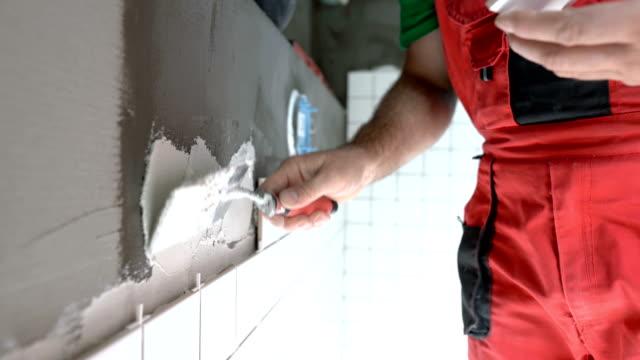 Mason laying tiles on the bathroom wall