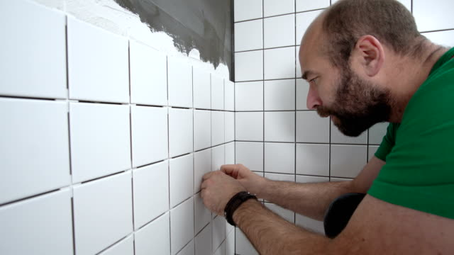 Mason removing tile spacers from installed tiles