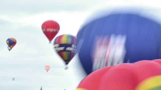 vídeos de stock, filmes e b-roll de mass assent of hot air balloons at the bristol international balloon fiesta over 100 balloons were successfully launched - festa do balão de ar quente