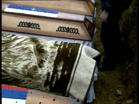 vídeos de stock e filmes b-roll de mass grave uncovered in kamenica / funerals / priests along in grave to bless and scatter earth on coffins / man covering coffin with rug mat / more... - 1993