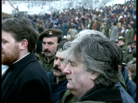 stockvideo's en b-roll-footage met mass grave uncovered in kamenica / funerals / radovan karadzic holding candle as he stands amongst serbian soldiers and orthodox priests / view of... - 1993