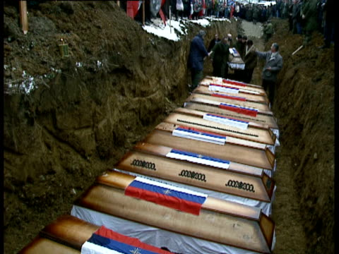 mass grave uncovered in kamenica / funerals / serbian troops standing by graveside with wooden crosses and wreaths / burial ceremony, more coffins... - bosnian war stock videos & royalty-free footage