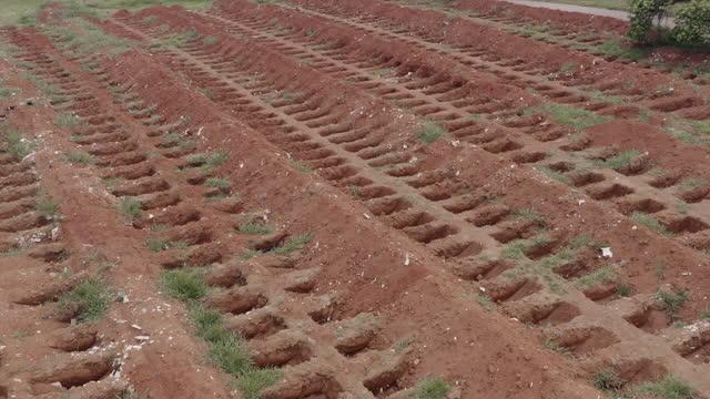 vídeos de stock, filmes e b-roll de mass graves, covid-19 deaths - pobreza questão social