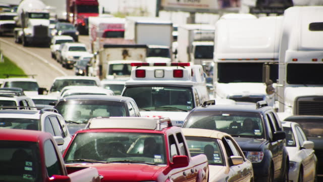 mass of vehicles create an early morning traffic congestion during rush hour on the interstate; an emergency ambulance is surrounded by cars and trucks. - ingorgo stradale video stock e b–roll