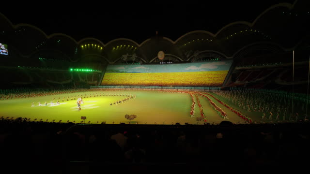mass perfomance in yellow light setting during mass games in pyongyang, north korea, dprk. wide shot - spoonfilm stock-videos und b-roll-filmmaterial