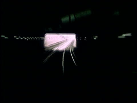 1975 MONTAGE Mass transit train entering and traveling through underground tunnel then traveling down track alongside busy road / United States
