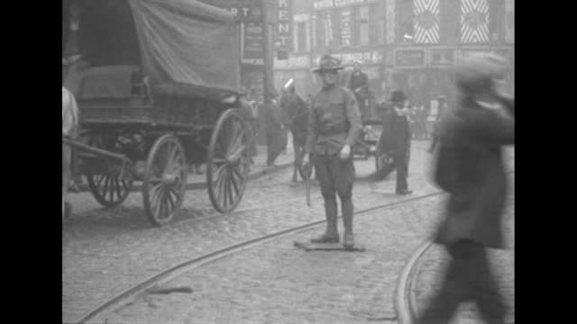 vídeos de stock e filmes b-roll de a massachusetts national guardsman directs traffic on a busy boston brick street with horsedrawn carts rolling past / note exact day not known - dirigir