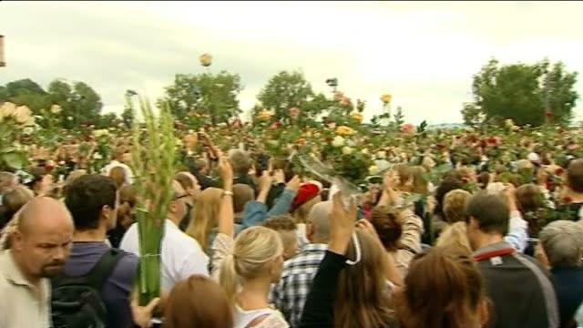 stockvideo's en b-roll-footage met massacre gunman anders breivik appears in court norway oslo ext pan across crowd of people holding up flowers at vigil people holding up roses mass... - anders behring breivik
