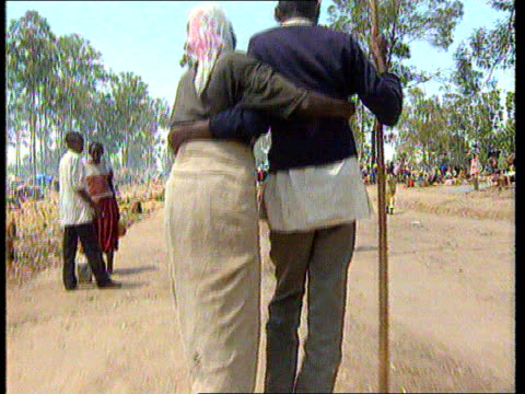 vídeos de stock e filmes b-roll de massacre in nyatama; rwanda: ruhango: starving refugees from civil war in rwanda helping each other along dirt road labv old couple helping each... - esfomeado