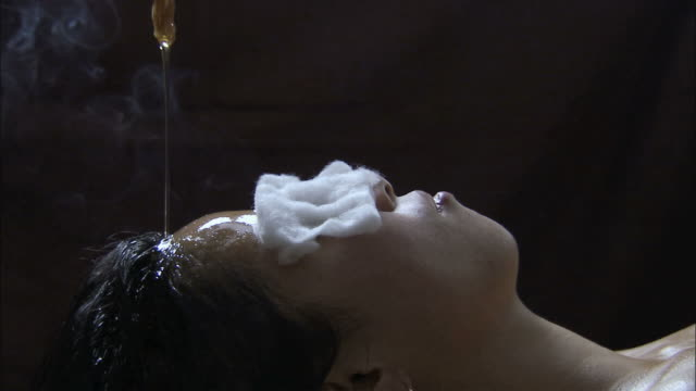 ms cu zi massage oil drizzling on young woman's forehead / india - forehead stock videos and b-roll footage
