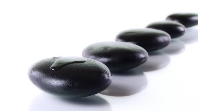 vídeos de stock, filmes e b-roll de hd: vazamento de óleo de massagem com pedras de seixos - lastone therapy