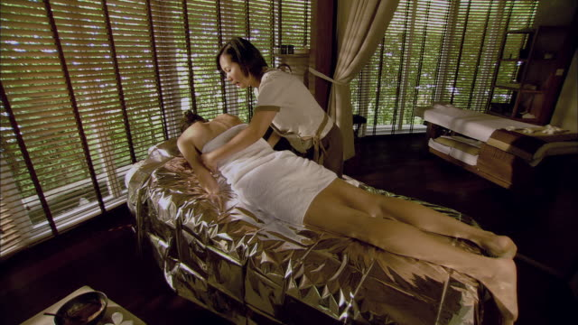 vídeos de stock, filmes e b-roll de ws massage therapist adjusting towel on woman lying on massage table covered with foil / hua hin, thailand - tratamento em spa