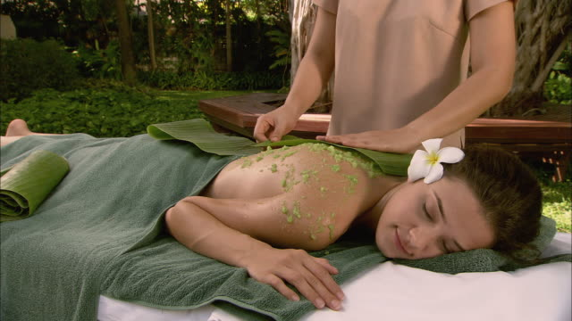 ms massage therapist applying banana leaf to woman lying on massage table / hua hin, thailand - massage table stock videos & royalty-free footage