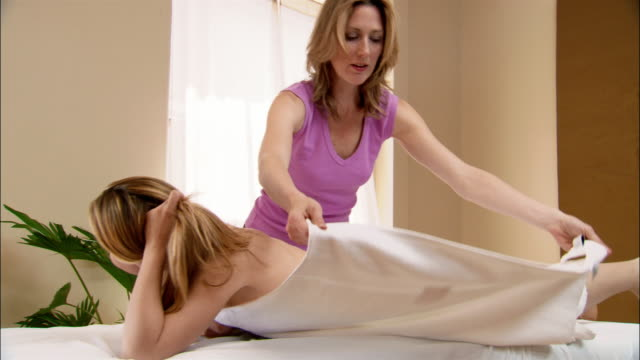 vídeos y material grabado en eventos de stock de massage therapist covering woman lying on massage table with towel - massage table