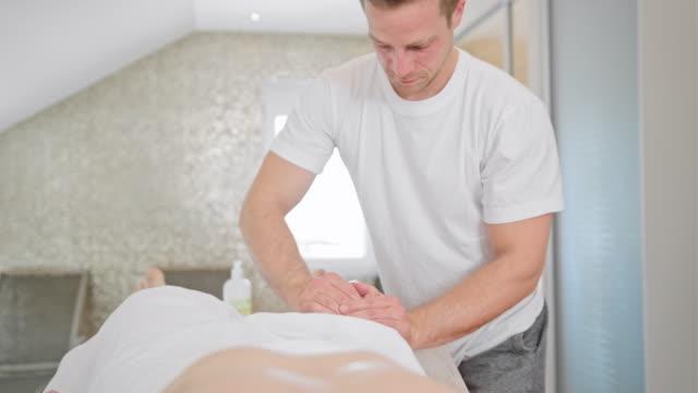 vídeos de stock e filmes b-roll de massage therapist massaging a man's leg - massagem