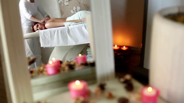 vídeos y material grabado en eventos de stock de terapia de masajes de masajes a una mujer joven. - masajista
