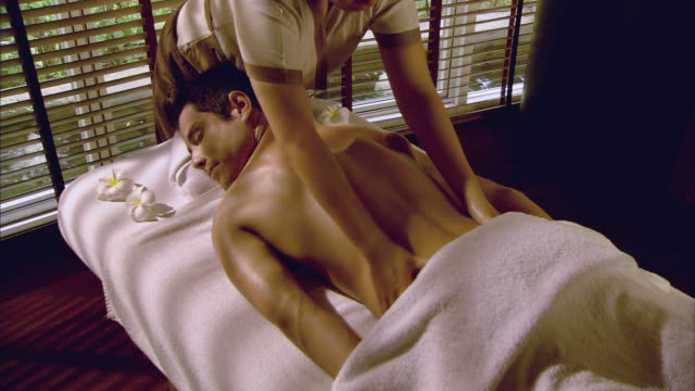 ms massage therapist massaging man lying on massage table / hua hin, thailand  - massage table stock-videos und b-roll-filmmaterial