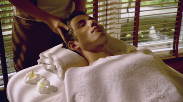 vidéos et rushes de cu massage therapist massaging man's head on massage table / hua hin, thailand - spa treatment