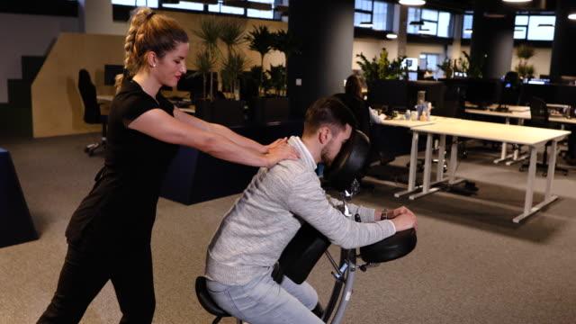 vídeos de stock e filmes b-roll de massage therapist massaging tired young businessman on his work break - dor no pescoço