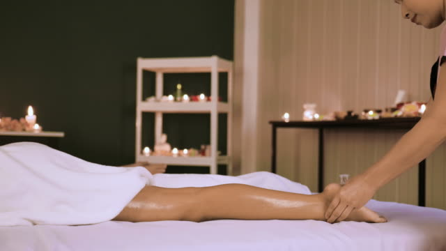 massage therapist massaging woman calves in spa center - osteopath stock videos & royalty-free footage