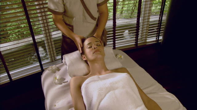 vidéos et rushes de ha ms massage therapist massaging woman's head on massage table / hua hin, thailand - massage room