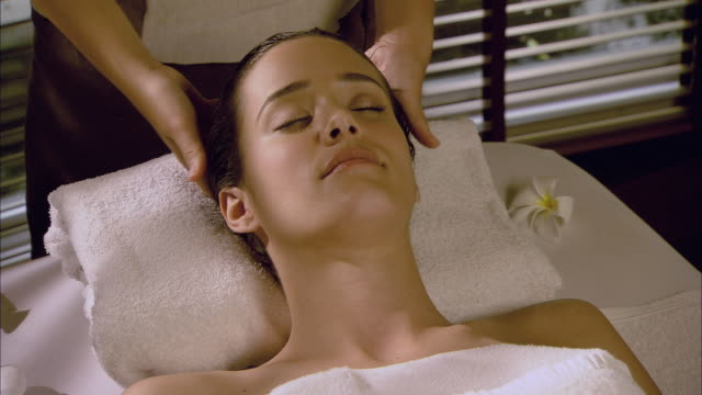 vidéos et rushes de cu massage therapist massaging woman's head on massage table / hua hin, thailand - massage room