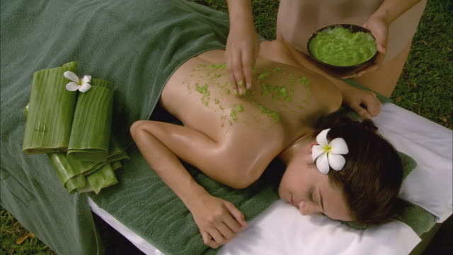 ha ms massage therapist rubbing cucumber and aloe on woman lying on massage table / hua hin, thailand - massage table video stock e b–roll