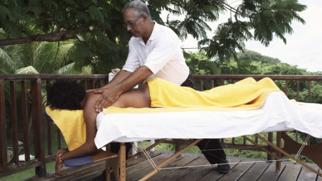 ms massage therapist rubbing woman's back, arnos vale, tobago, trinidad and tobago - massage table stock videos and b-roll footage