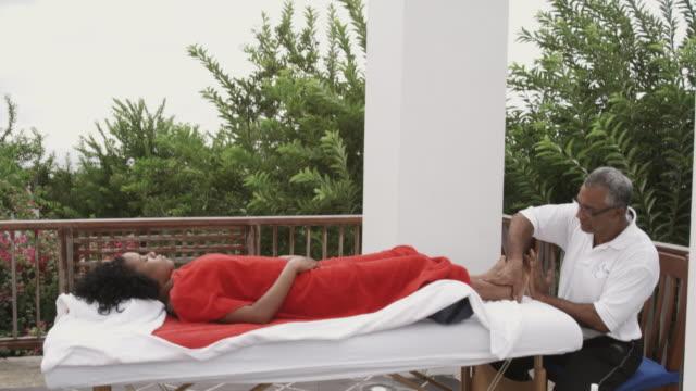 stockvideo's en b-roll-footage met ms td massage therapist rubbing woman's feet, arnos vale, tobago, trinidad and tobago - in een handdoek gewikkeld