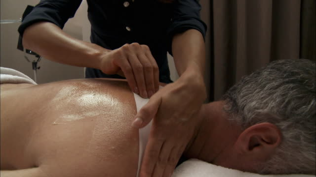 vídeos de stock e filmes b-roll de cu massage therapist waxing customer's back / brussels, belgium - depilação