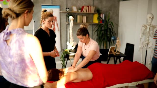 vidéos et rushes de professeur de massothérapie montrant à l'élève comment bien mettre sa main pour le massage - banc de massage