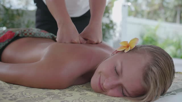 massage woman by a masseuse hands at a resort hotel spa. - slow motion - masseur stock videos & royalty-free footage
