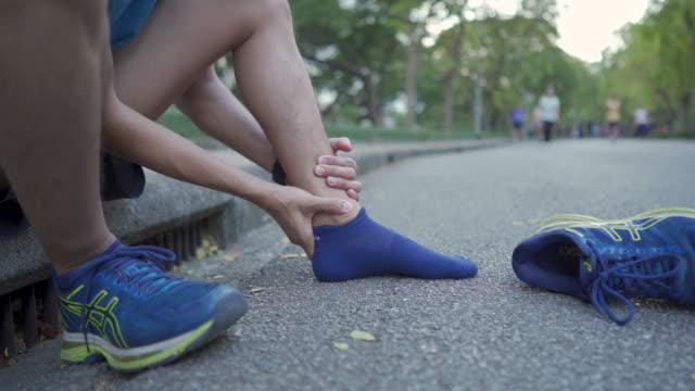 vídeos de stock e filmes b-roll de massaging leg and ankle pain before exercise - musculado
