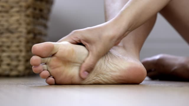 massaging sore foot - wooden floor stock videos & royalty-free footage