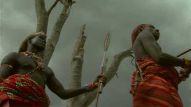 massai men stand watch on a windy african plain. - feierliche veranstaltung stock-videos und b-roll-filmmaterial
