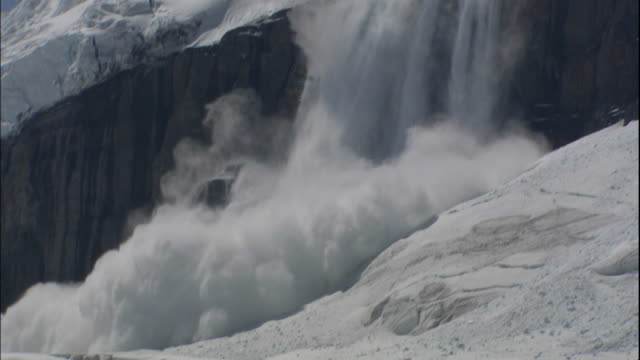 masses of ice falls down cliff from columbia icefield, canada - icefall stock videos and b-roll footage