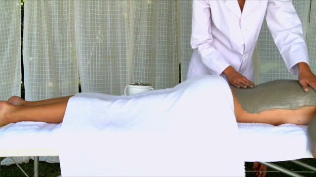 ms pan masseur applying body mask on woman's back / cape town, south africa - マッサージ台点の映像素材/bロール