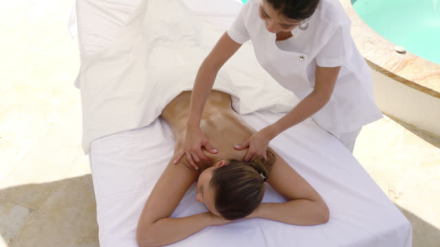 masseuse doing a back massage at a spa outside - pampering stock videos & royalty-free footage