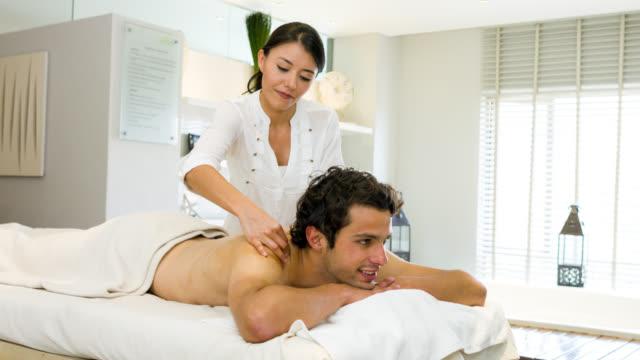 Masseuse doing a back massage on a man
