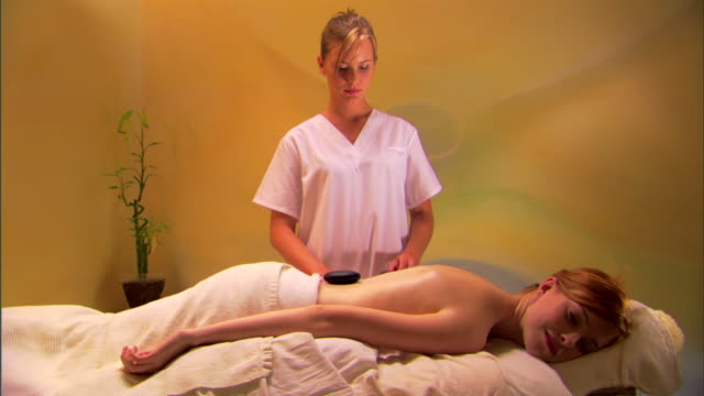 masseuse giving woman stone massage treatment - lastone therapy stock videos and b-roll footage