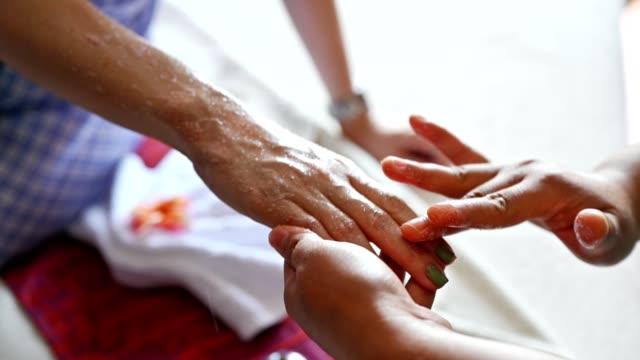 vidéos et rushes de masseuse utilise l'huile de sel à base de plantes à frottis sur le dos de la main de la jeune femme - se frotter