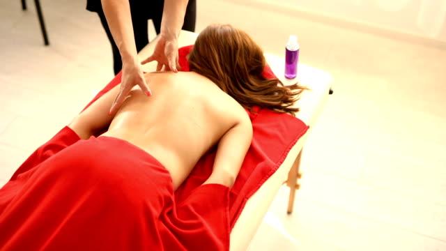 vidéos et rushes de masseuse masser une cliente avec de l'huile de massage essentielle - banc de massage
