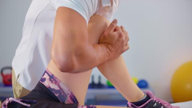 stockvideo's en b-roll-footage met slo mo masseuse masseert de knie van een vrouwelijke klant - massagetafel