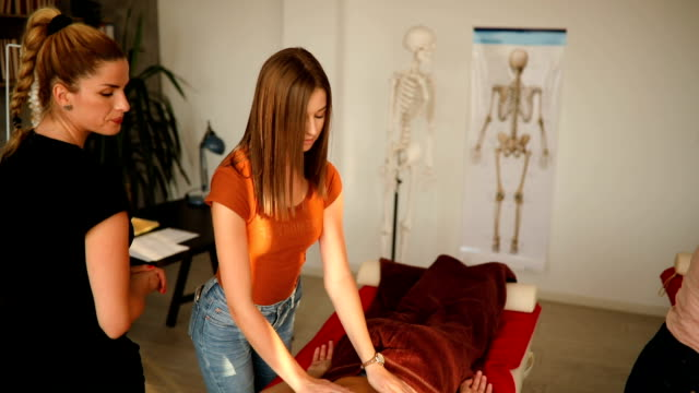 vidéos et rushes de masseuse observant son élève pendant qu'ils pratiquent le massage sur le client - banc de massage
